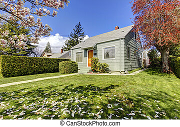 Small green house exterior with spring blooming trees.