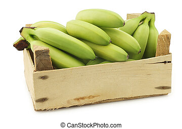 small green snack bananas in a wooden crate