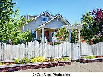 Small grey craftsman style home behind white fence.