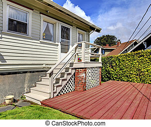 Small grey house with staircase to back yard deck.
