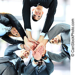 Small group of business people joining hands, low angle...