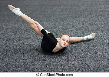 Small gymnast trains in the gym