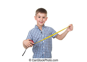 Small handsome builder boy dressed in blue checkered shirt holds a measuring tape, isolated on white background.