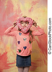 small happy baby girl holding valentines day decorative pink heart