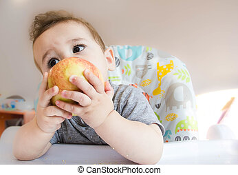 small happy child sitting in a chair and eats Apple from whose face is marred in baby food, the concept of family, child health, feed the baby, eat at home, funny expression face