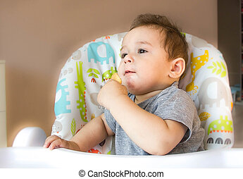 small happy child sitting in a chair and eats cookies from whose face is marred in baby food, the concept of family, child health, feed the baby, eat at home, funny expression face