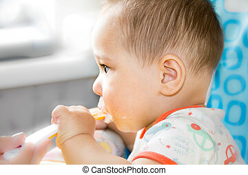 small happy child sitting in a chair and eats yogurt from whose face is marred in baby food