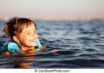 Small happy girl swimming and having fun in clear sea water with rocks at background