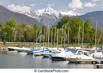 Small harbour on a lake with snow-capped mountains