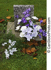 Purple and white flowers on a grave, Batsford church, Gloucestershire, England, uk