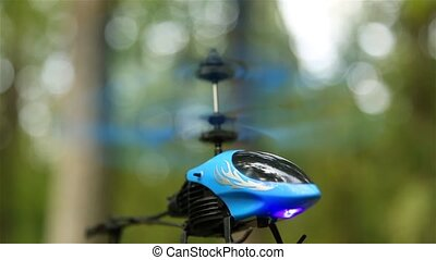 Small toy helicopter in the forest outdoors hovering in the air HD 1920x1080