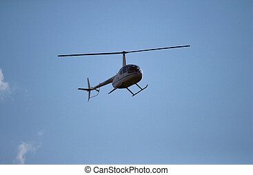 Small helicopter on blue sky
