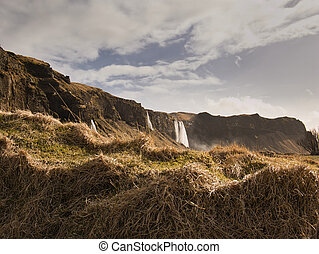 Small hill with waterfalls in the background