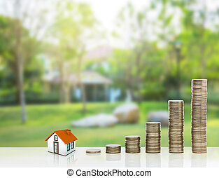 Small house and gold stack coins. The concept of purchase of...