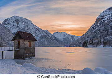 Small house in frozen lake Predil with sunset in winter -...