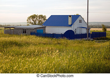 Small house in village with a dark blue roof