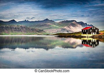 Small house on river bank in Iceland