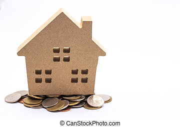small house standing on coins. The concept of purchase of habitation.