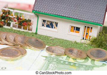 small house with euro coins and banknote