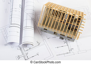 Small house under construction and electrical drawings, concept of building home