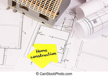 Small house under construction and rolls of electrical diagrams or blueprints, building home concept