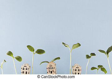 small house with growing young plants on blue background