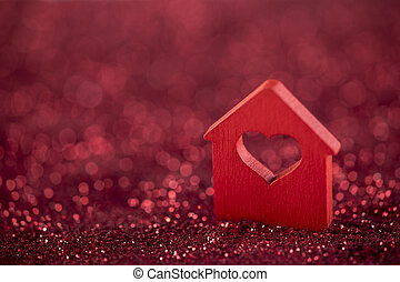 Small house with heart shape on red glitter background