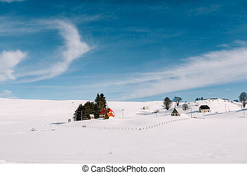 Small houses in a hilly area, in the winter on the snow against a blue sky with cirrus clouds.