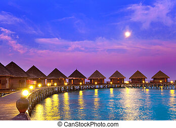 small houses on water on a sunset