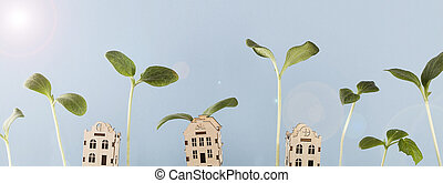 small houses with growing young plants and glare of sun on blue background