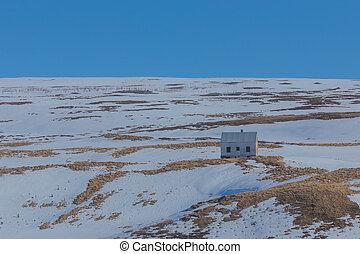 Small hut on snow hill