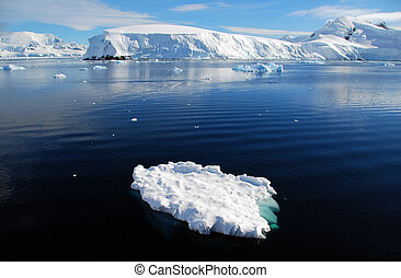 small iceberg in front of frozen antarctic landscape