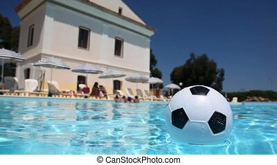 Small inflatable soccer ball floats in the pool