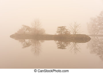 Small island in the fog on the water