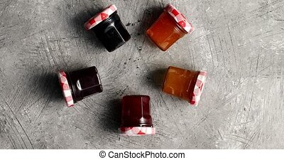 Small jars with various marmalade - Top view of small glass...