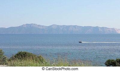 Small jetty boat is crossing over calm sea.