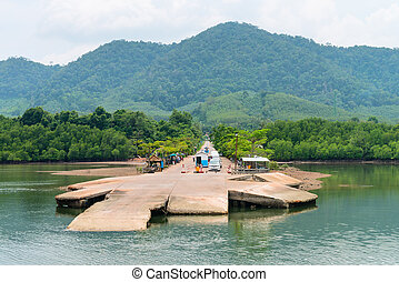 Small jetty for ferry on green tropical island with cars in...