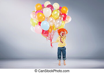 Small jumping boy holding bunch of balloons