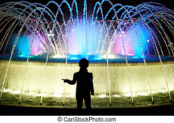 Small kid play with colorful fountain