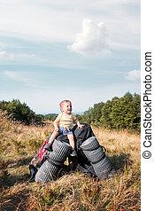 Small kid sitting on tourists backpacks