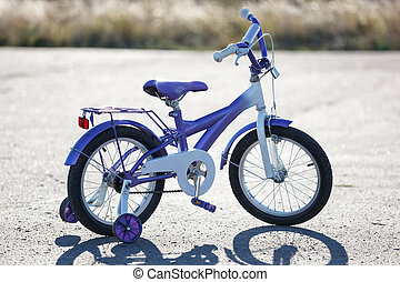Small kids bike with training wheels outdoors.