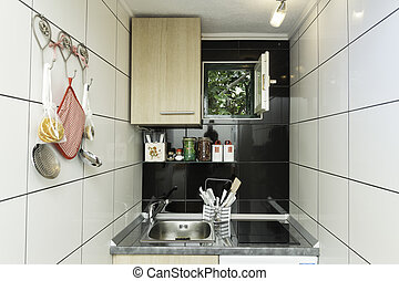 Small kitchen with white tiles on the wall