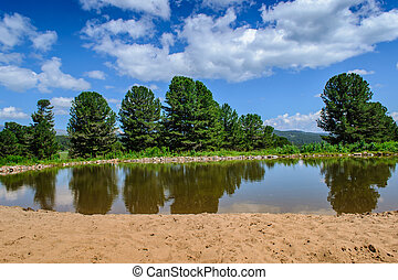 small lake in mountains with sandy beach on sunny day