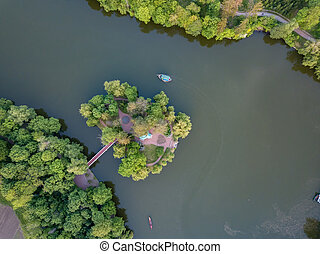 small lake in the middle of a forest and an island with a bridge, top view