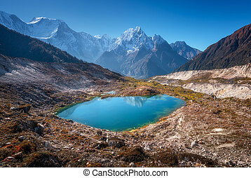 Small lake with blue water and snow covered mountains