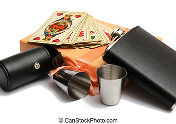 small leather hip flask with two metal mug and old playing cards at orange giftbox
