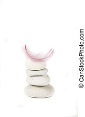 small light beautiful pink feather lying on a pile of gray stones