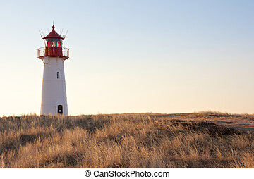 Small lighthouse at dusk - Small white lighthouse on a hill ...