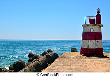 Small lighthouse on the ocean shore