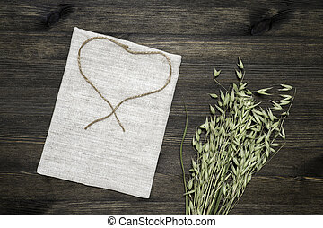 Small linen bag knotted with jute twine and green ears of oats on a dark wooden background.